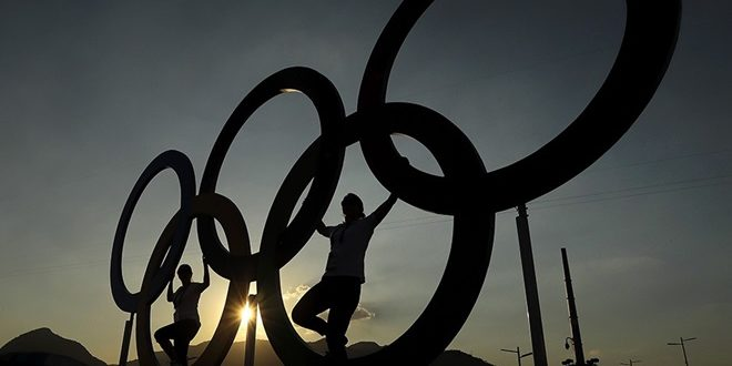 People pose for a photo with the Olympic Rings at the Olympic Park in Rio de Janeiro, Brazil, Monday, Aug. 1, 2016. The Summer 2016 Olympics is scheduled to open Aug. 5. (AP Photo/Charlie Riedel)